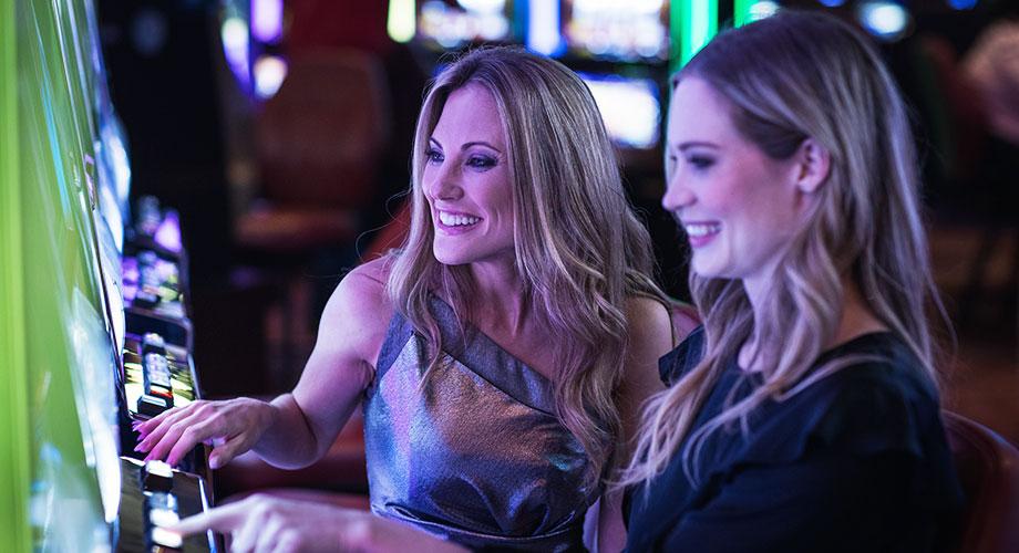Two women playing slots