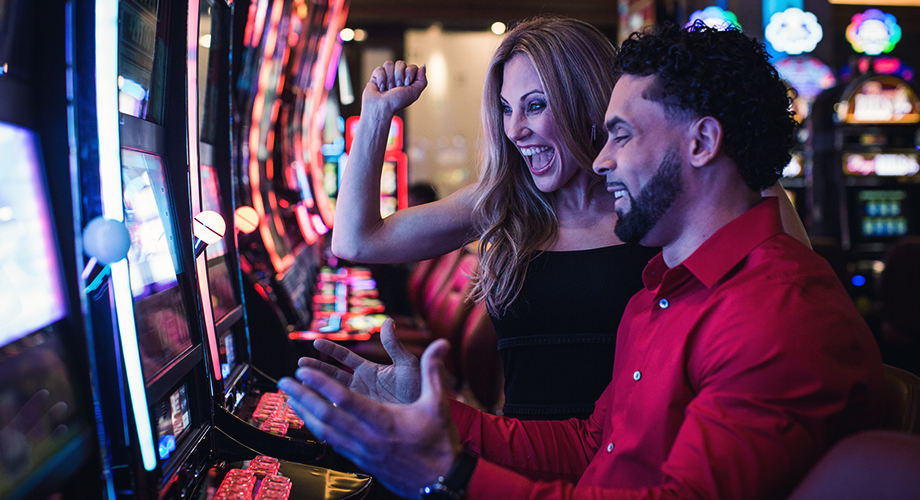 A couple playing the slots