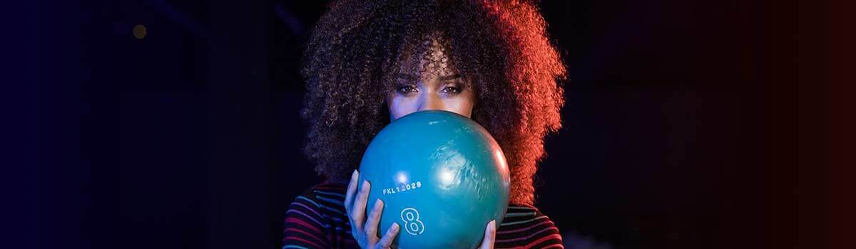 Woman with bowling ball in front of her face