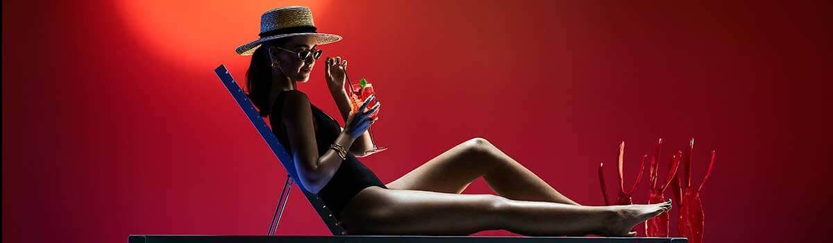 Silhouette of a woman in a pool chair drinking cocktail